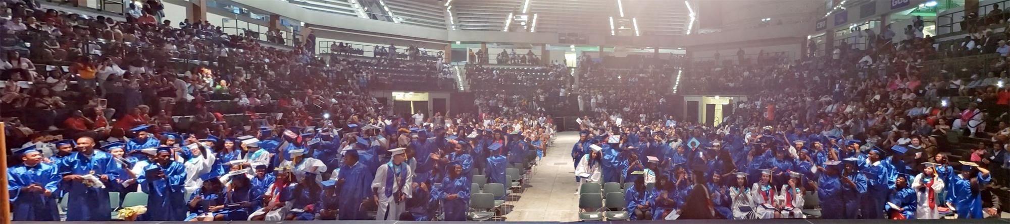 Photo of seniors in cap and gown at graduation.