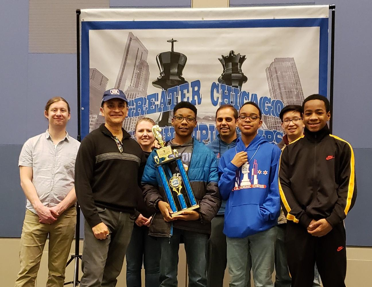 Brooks' AC Chess Team in front of the Citywide Competition Banner.