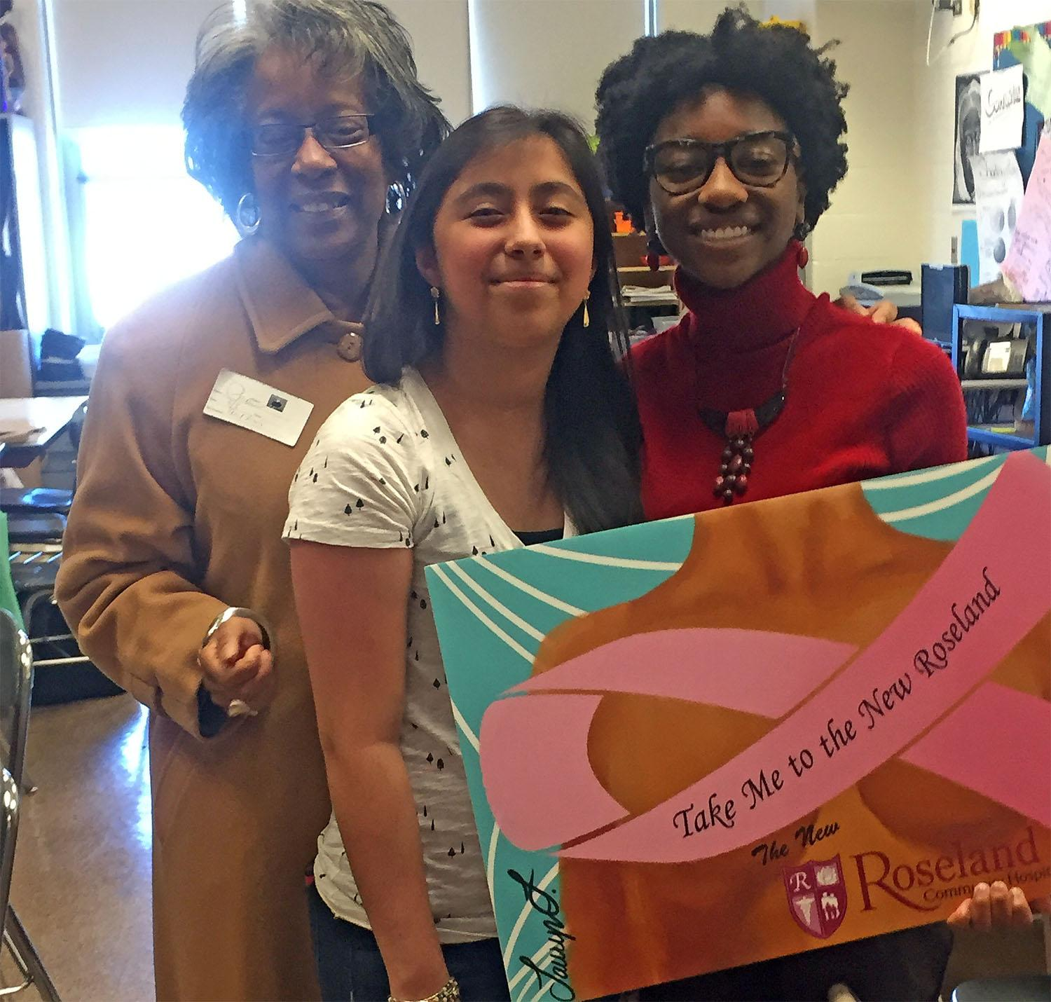 Rhonda Purdue from Roseland Hospital with Lauryn Freeman and Andrea Perez, holding Lauryn's logo.