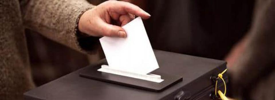 Hand putting vote in ballot box.