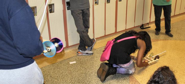 Photo of students competing with ther cars made with CDs, a mouse-trap and sticks.
