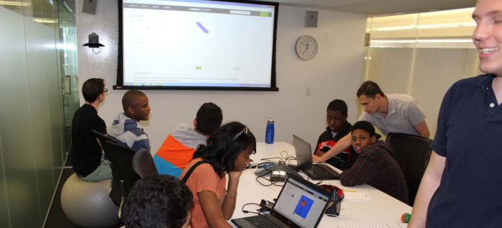 Photo of students working with IMC's programmers.