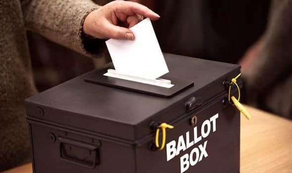 Photo of a hand putting vote into ballot box.