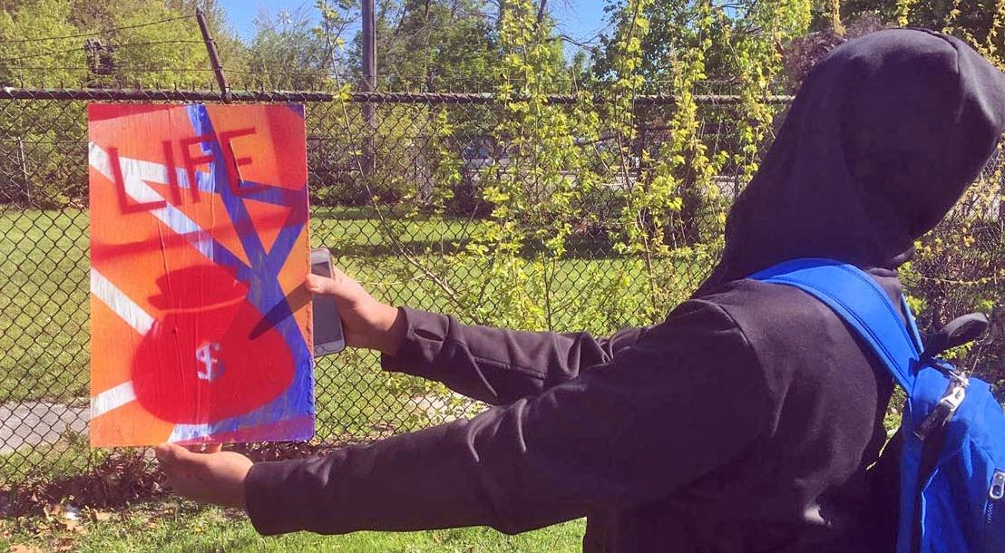Student holding a spray paint project he created.