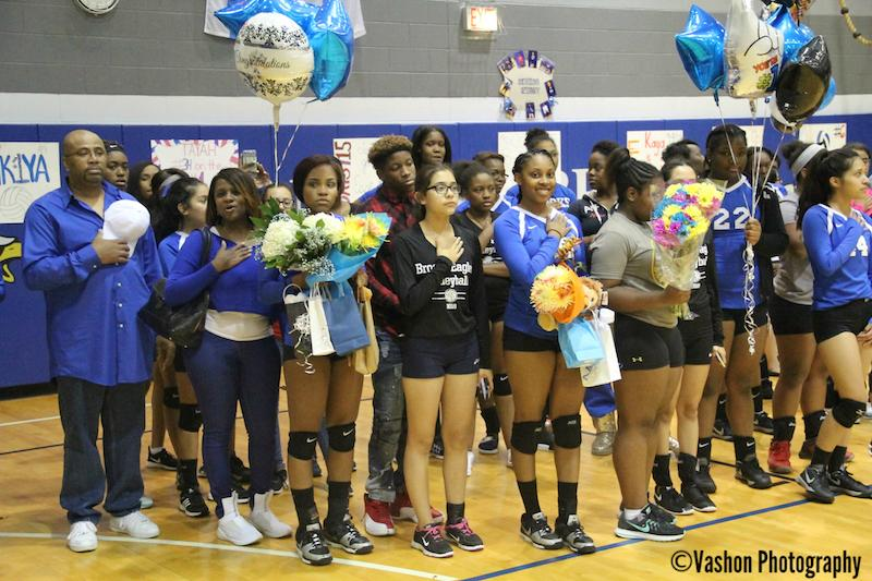 Photo of volleyball team with parent and balloons.